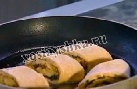 Выкладываем кусочки рулета на сковороду с оставшимся растопленным маслом и обжариваем с обеих сторон.