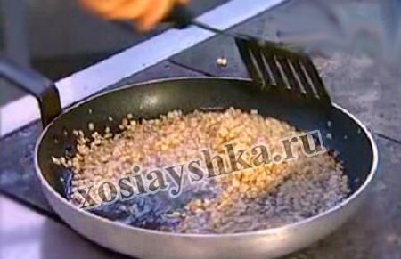 В это время займемся начинкой. Из лука и зелени она поучится не только бюджетной, но и очень вкусной. Рулет без шкварок будет суховатым, а вот шкварки пропитают и наше тесто и начинку. Сало мелко нарезаем и растапливаем на сковородке. К нему отправляем мелко нарезанный лук, затем добавим измельченную петрушку. Ее тоже обжарим в сале.